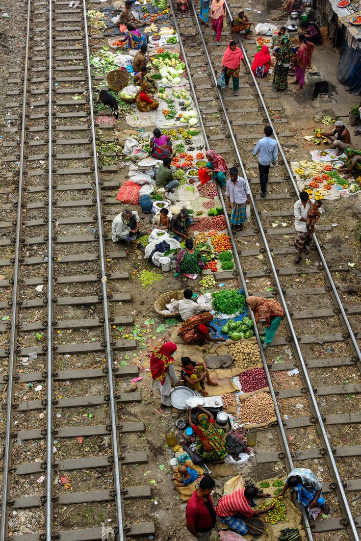 This is a portable vegetable market. When any train comes they just moved from their position. This is the cheapest vegetable market and most of the customers are from the slum nearby. Taken from Tejgaon industrial area, Dhaka, Bangladesh.