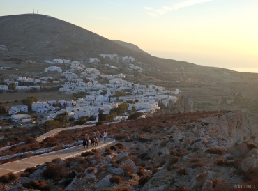 The view of Chora and people climbing with donkeys in sunset light
